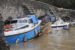 © Licensed to London News Pictures. 27/12/2013<br /> Damaged boats riverside at East Farleigh pushed into East Farleigh bridge. near Maidstone, Kent.<br /> East Farleigh flood water in Kent has receded leaving locals counting the cost of the damage.<br /> Flood water starts to recede over night across Kent.<br /> Photo credit :Grant Falvey/LNP
