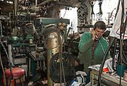 Metal artist in his busy workshop.