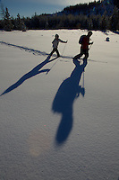 Russell Laman (age 12) and Jessica Laman (age 9)  cross-country skiing below the Teton Range, cast long shadows in the afternoon light.<br />Grand Teton National Park, Wyoming