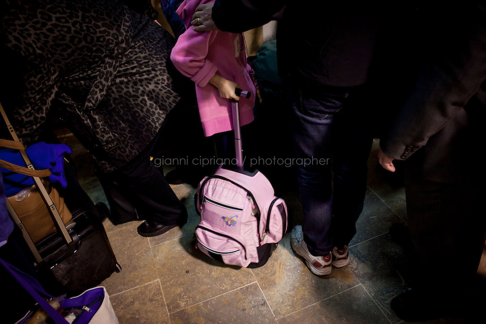 25 February 2011. Valletta, Malta. A girl nexter to her dad waits at the Maltese Customs after stepping down from the ferry that evacuated them from Libya. A U.S.-chartered ferry evacuated Americans and other foreigners out of Libya on Friday and brought them to the Mediterranean island of Malta. The Maria Dolores ferry, after three days of delays, brought over 300 passengers, including at 167 U.S. citizens, away from Libya where Colonel Gaddafi's forces continue to clash with anti-government demonstrators.<br /> <br /> <br /> &copy;2011 Gianni Cipriano<br /> cell. +1 646 465 2168 (USA)<br /> cell. +39 328 567 7923<br /> gianni@giannicipriano.com<br /> www.giannicipriano.com