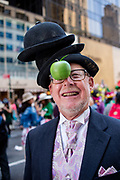 New York, NY - April 16, 2017. A man wears a stack of bowler hats and a green apple, and looks like Rene Magritte's 1946 painting The Son of Man at New York's annual Easter Bonnet Parade and Festival on Fifth Avenue.