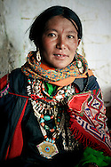 India, Ladakh. Portrait of a woman from Korzok attending the local festival and wearing a traditional dress.
