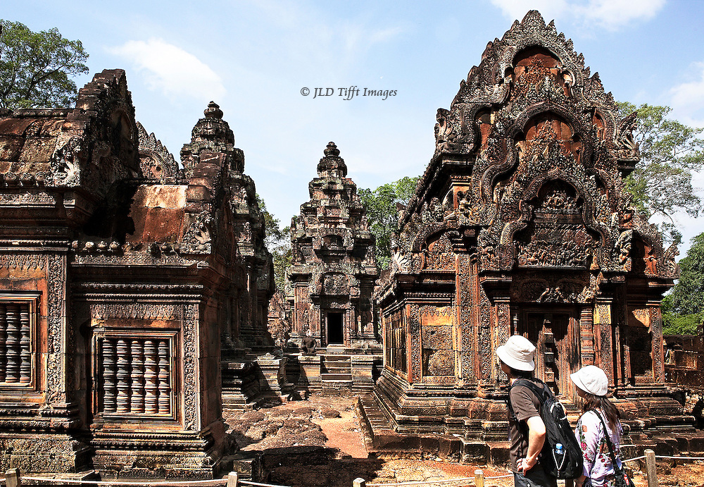Angkor, Banteay Srei:  cluster of central sanctuaries and other structures; two tourists in white hats in the foreground..