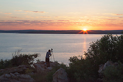 A tourist photographs the sunrise from Hall Point in Camden Sound.