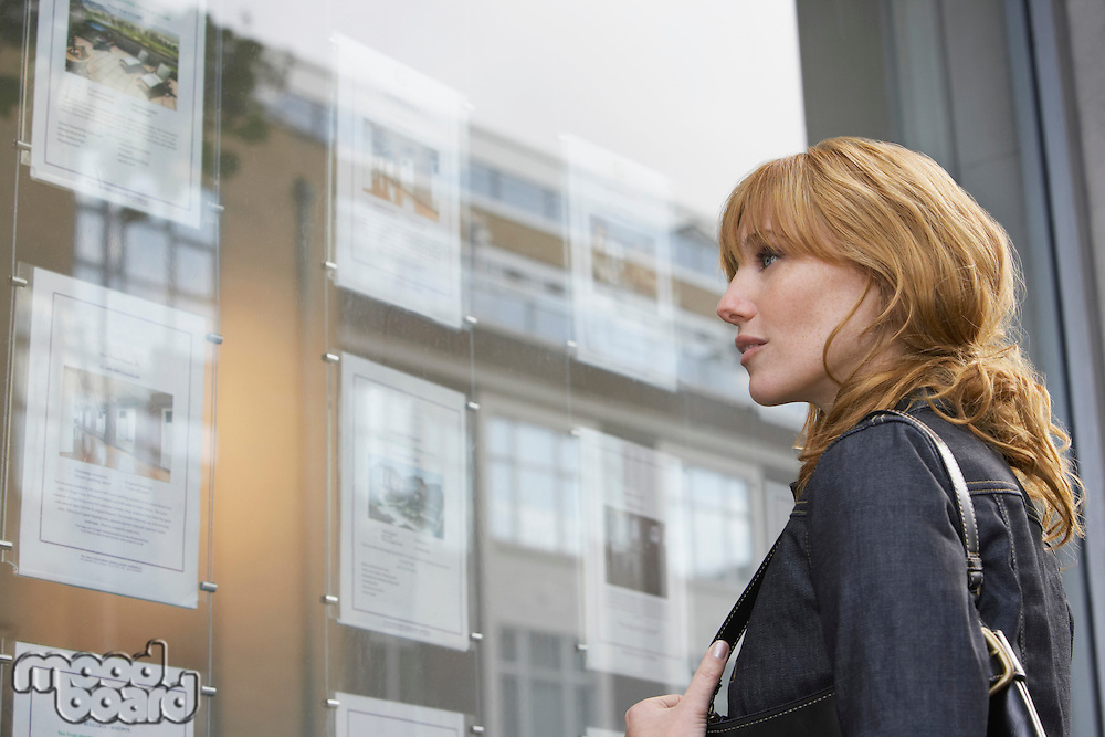 Woman looking in window outside estate agents