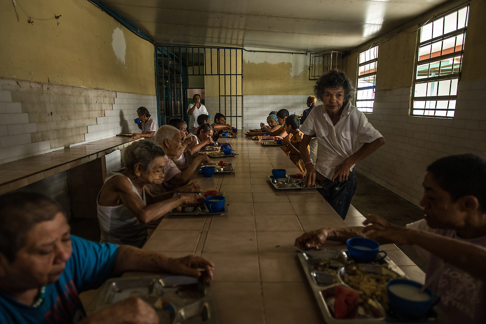 BARQUISIMETO, VENEZUELA - JULY 29, 2016: Patients wait to eat lunch: pasta, milk and a slice of watermelon, in the women's ward. The economic crisis that has left Venezuela with little hard currency has also severely affected its public health system, crippling hospitals like El Pampero Psychiatric Hospital by leaving it without the resources it needs to take care of patients living there, the majority of whom have been abandoned by their families and rely completely on the state to meet their basic needs. The hospital has not employed a psychiatrist for over two years. The halls are filled with sounds of patients crying or screaming, and an overpowering stench of urine and feces. There is a shortage of food, and drugs used to combat bipolar disorder, epilepsy, schizoaffective disorder and chronic anxiety are now in short supply, as are numerous sedatives and tranquilizers needed to care for patients. PHOTO: Meridith Kohut