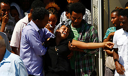 Selemauit Hagus Belay (C) of Ethiopia cries as a hearse carrying the coffin of her Eritrean husband Ashih Tekleab Haile leaves Mater Dei Hospital outside Valletta July 26, 2011. Ashih, who arrived in Malta as an irregular immigrant with his wife in 2009, drowned on July 20 after rescuing a French tourist from drowning in rough seas. The Maltese government subsequently announced it would amend a law to enable it to award Ashih a posthumous medal for bravery, currently only available for Maltese nationals, according to local media.<br />