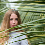 Portrait of a young girl with blonde long hair in palm trees.