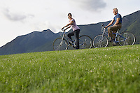 Man and woman biking mountain range in background