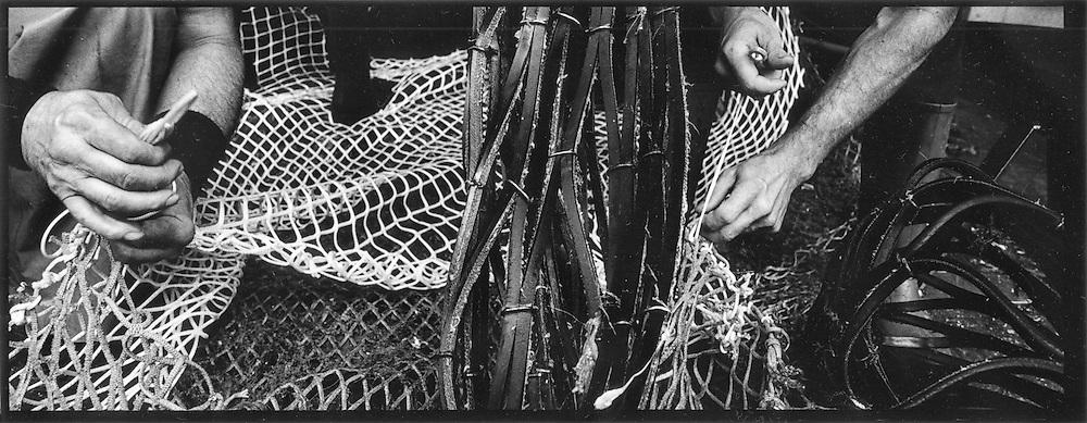 Due pescatori riparano le reti per la pesca<br /> <br /> Two fishermen repair their nets for fishing