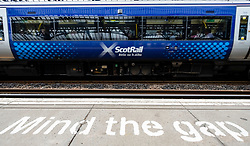 View of Scotrail passenger train at station platform with Mind the Gap warning painted on edge, Stirling, Scotland, UK