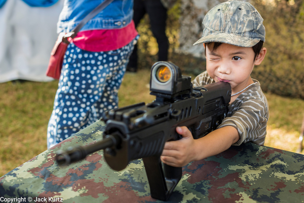 "11 JANUARY 2014 - BANGKOK, THAILAND:  A Thai boy plays with a TAVOR Assault Rifle during Children's Day in Bangkok. The Royal Thai Army hosted a ""Children's Day"" event at the 2nd Cavalry King's Guard Division base in Bangkok. Children had an opportunity to look at military weapons, climb around on tanks, artillery pieces and helicopters and look at battlefield medical facilities. The Children's Day fair comes amidst political strife and concerns of a possible coup in Thailand. Earlier in the week, the Thai army announced that movements of armored vehicles through Bangkok were not in preparation of a coup, but were moving equipment into position for Children's Day.     PHOTO BY JACK KURTZ"