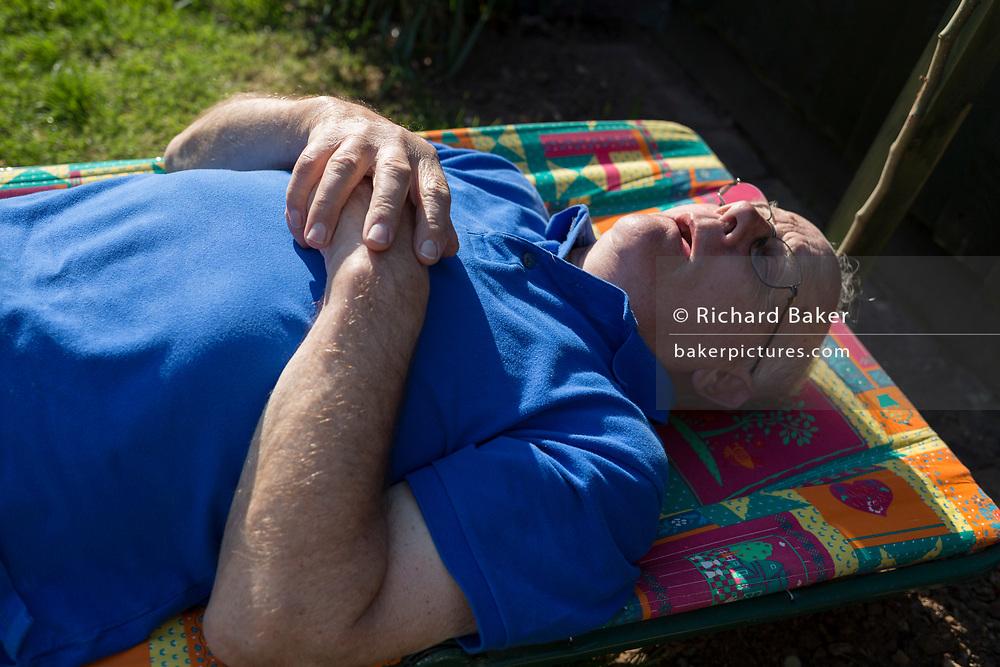 An elderly man in his eighties sleeps horizontally in spring sunshine, on a sun lounger in his rear garden on 21st April 2019, in Nailsea, North Somerset, England