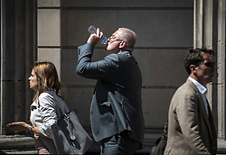 © Licensed to London News Pictures. 25/06/2018. London, UK. A man takes a swig of water as he walks past the Bank of England as high temperatures remain in most of the UK. Photo credit: Peter Macdiarmid/LNP