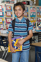 School boy holding book in classroom, portrait