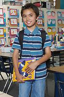 School boy holding book in classroom, portrait