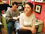 Picture by Mark Larner. Picture shows John about to tattoo customer Haley at Diamond Jacks tattoo studio in Soho, London...London College of Printing BA (Hons) degree project on tattooing 1999-2000