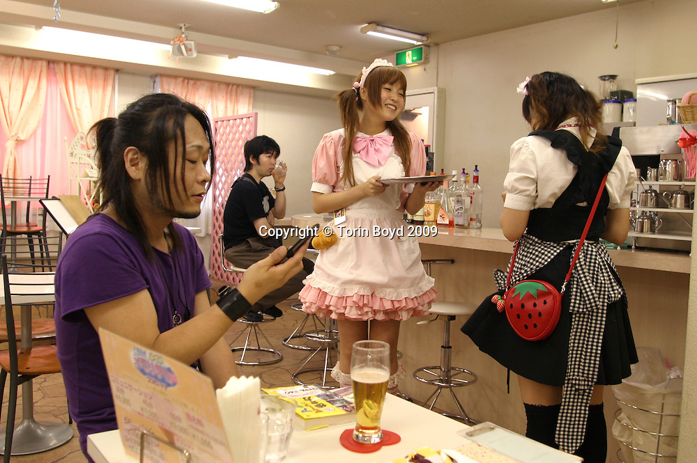 "Ayana (pink uniform), who works at Royal Milk Cafe and Aromacare six days a week only goes by her first name. When asked her age she replied ""eien juhasai"" which in Japanese means ""forever 18"".  She has been working here for one year. The customer (in purple t-shirt) is 27 year old Keisuke Masaki, a hair stylist who was visiting here on his day off. This was his seventh visit to Royal Milk but he commented ""its so enjoyable here, if I couldn't come anymore it would be really sad""...Background:  This is Royal Milk Cafe and Aromacare, a maid cafe located in Tokyo's electronic district of Akihabara. Here cute young women clad in frilly maid uniforms literally wait on customers hand and foot, offering a fantasy experience inspired by manga and anime heroines. Mostly a hangout for ""otaku"", the Japanese term for geeks and social outcasts who identify more with the virtual world than regular life, Royal Milk caters to their concept of ""moe"", the attraction to characters in the anime, manga and video game fantasy worlds...Besides the popular entrance greeting of ""welcome home my master"", services here include simple and inexpensive cafe food, aroma therapy called ""body care"" and ""foot care"", and one-on-one chats in a private rooms. This hanky-panky free service ranges in price from 2000 JPY ($18) to 9000 JPY ($78), depending on the duration...Japanese maid cafes first sprang up in Tokyo's Akihabara district in 2001, and there are now over 30 of them in the area. But this is just a tip of the iceberg for Japan's otaku industry which has 3 million consumers who spend an estimated $5 billion annually. Most otaku are men between the ages of 18 to 45 but current trends show more women are among them...Royal Milk opened in June 2005 and normally has four to six maids working at all times and can be found on the web at: http://r-milk.com."
