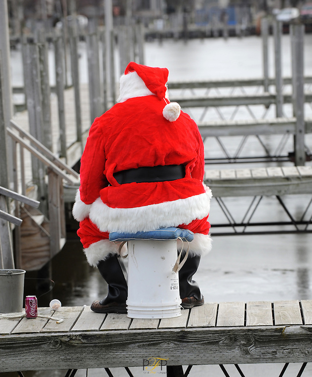 Santa fishes for perch through the ice on the docks at Lakeside Park. Tuesday, December 20, 2011. The Reporter photo by Patrick Flood.