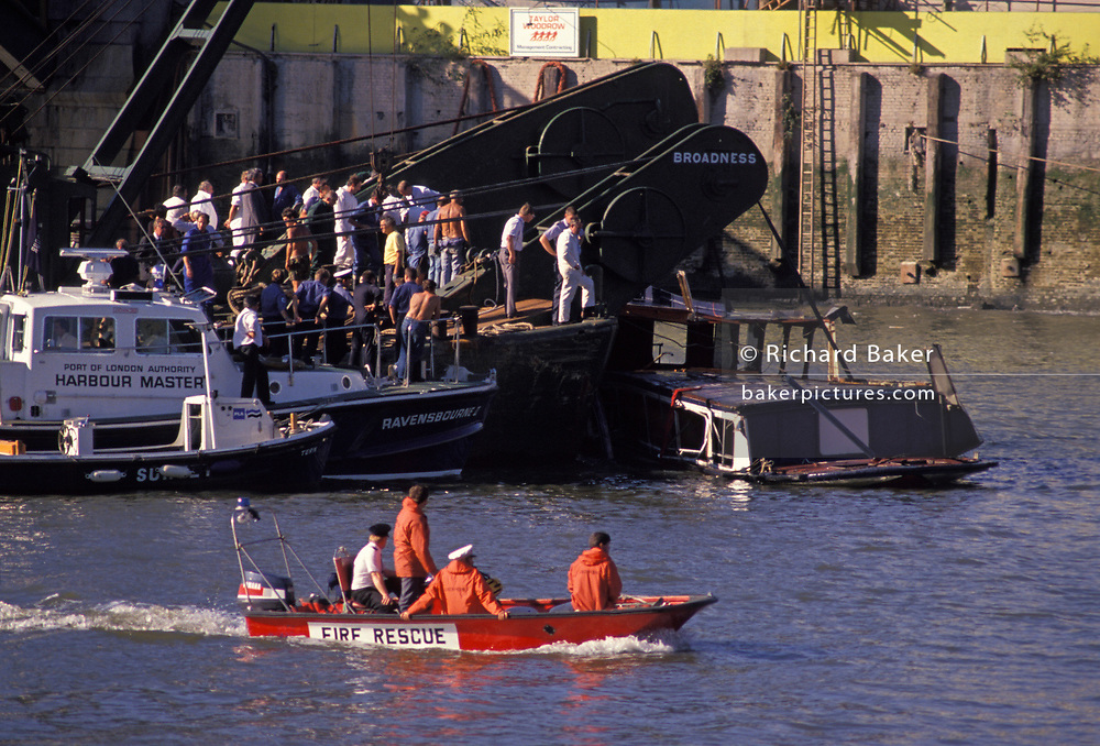 A fire rescue boar passes forensic investigators and police officers looking over the wreckage of The Marchioness pleasure boat, on 20th August 1998, river Thames in London, England. The Marchioness disaster resulted in a fatal collision between two vessels on the River Thames in London on 20 August 1989, which resulted in the drowning of 51 people. The pleasure steamer Marchioness sank after being pushed under by the dredger Bowbelle, late at night close to Cannon Street Railway Bridge.
