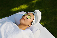 Young woman with cucumbers over eyes, lying on massage table outdoors