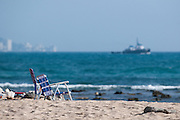 Empty beach chairs sit in the sand on Sand Island as a ship passes in the distance.