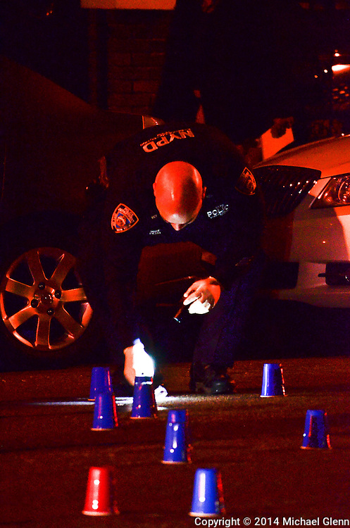 Brooklyn, New York - November 302014: Crime scene investigator examines items on ground on the scene of reports of 3 people shot  at 375 Remsen Ave  in New York, New York. Photo Credit: Michael Glenn / For the Daily News
