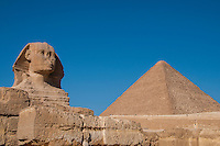Giza, Egypt - the Sphinx with a pyramid on the right against a blue sky.