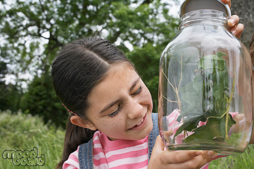 Girl (7-9) with eyes closed holding jar of stick insects close-up