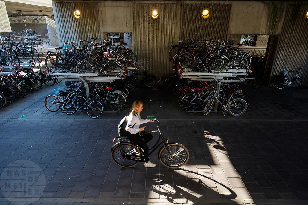 Een meisje fietst langs de volle fietsenstalling bij Amsterdam-Zuid.<br /> <br /> A girl passes the crowded bike parking near Amsterdam-Zuid.