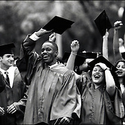 Happy smiling multi-racial faces of new New Yourk University graduating class holding up caps in Washington Square Park
