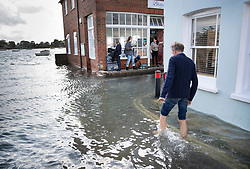 © Licensed to London News Pictures. 01/10/2019. Bosham, UK. A man wades through seawater as the high tide covers roads in the village of Bosham in West Sussex. Parts of the South are being affected by the aftermath of Hurricane Lorenzo with numerous flood warnings in place. Photo credit: Peter Macdiarmid/LNP