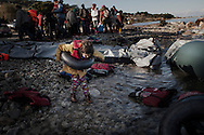 A young girl plays with a tire air chamber amid dinghy debris after she landed on Lesbos. Refugees from Afghanistan and Syria arrive in boats on the shores of Lesbos near Mytilene's airport, Greece on 08 January, 2016. Lesbos, the Greek vacation island in the Aegean Sea between Turkey and Greece, faces massive refugee flows from the Middle East countries.