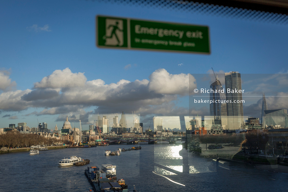 The reflections from the top deck of a London bus and in the background, the City of London and the river Thames, on 14th December 2017, in London, England.