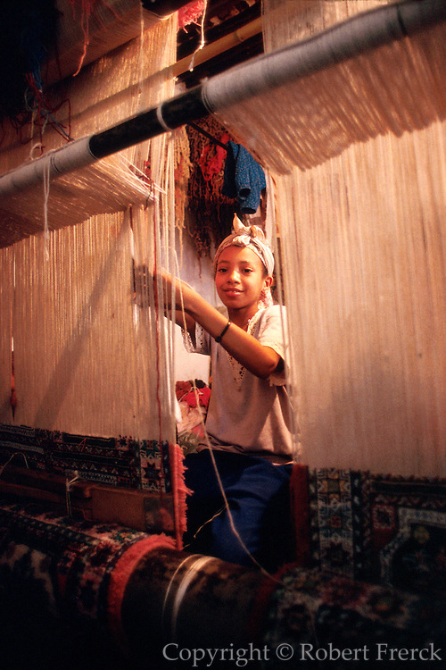 MOROCCO, FEZ young girls weaving a fine carpet on a  traditional upright loom in a carpet craft shop in the Medina