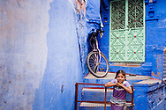 India, Jodhpur. A young girl near her painted blue house.