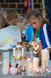 © Licensed to London News Pictures. 12/07/2017. LONDON, UK. A young girl lits candles during a vigil at the memorial wall by Latimer Station, west London, on Wednesday 12 July, 2017, to remember those killed in the Grenfell Tower fire four weeks on from the tragedy when around 80 people are thought to have been killed. Photo credit: ISABEL INFANTES/LNP
