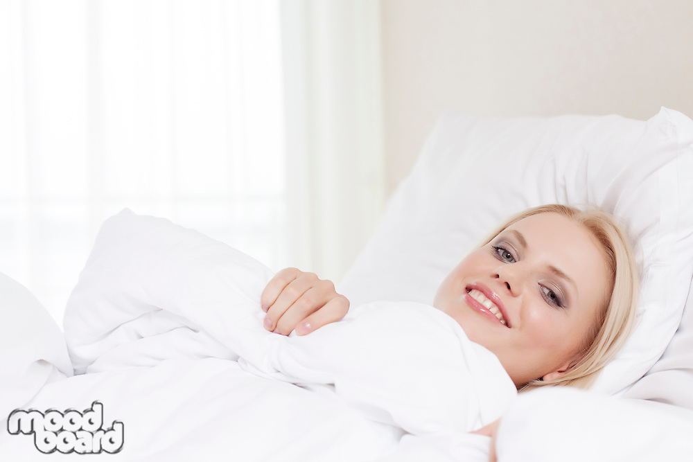 Portrait of beautiful young woman lying in hotel room