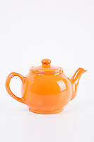 Close-up of orange kettle over white background