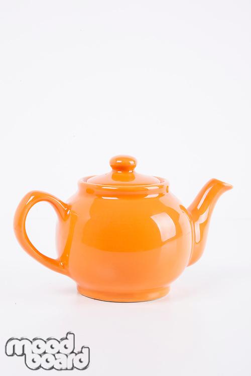 Close-up of orange kettle over white background