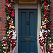 Outdoor Christmas large wooden toy soldiers decorations on both sides of front door of building.