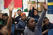 """Maxwell """"Bunchie"""" Young, 10, (center, orange hair) and his classmates all raise their hands, hoping to be chosen as a helper during class. Bunchie is in the fifth grade at KIPP Scholar Academy in South L.A. Known for his flair on the field and his signature look of frequently-changing hair color, school administrators recently asked him to dye his hair back to a normal color saying it was distracting."""