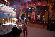 Cholon (Chinatown). Quan Am Pagoda. Worshippers burning inscense. An A Pho statue (m.)