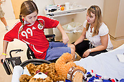 30 DECEMBER 2009 -- PHOENIX, AZ: Crystal Guidice (CQ) a Physical Therapist, helps Mackenzie Saunders into her wheelchair before taking her to Physical Therapy at St. Joseph's Hospital in Phoenix Wednesday. Mackenzie was knocked down by another player during a soccer game. She finished the game but later in the day her legs started hurting and her parents took her to a hospital. Three hospitals later, she was in St. Joseph's with a diagnosis of a swollen spine and she couldn't walk. Now she's in physical therapy. She is expected to make a full recovery but her doctors have said she won't be able to play soccer for at least another 16 months.  Photo by Jack Kurtz