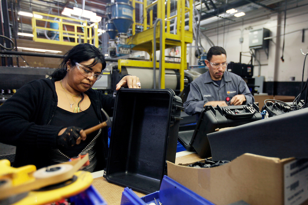 Workers install case lids and handles while assembling an injection-molded plastic hardshell case at the Pelican Products Inc. production facility in Torrance, California, U.S., on Thursday, March 8, 2012. © 2012 Patrick T. Fallon