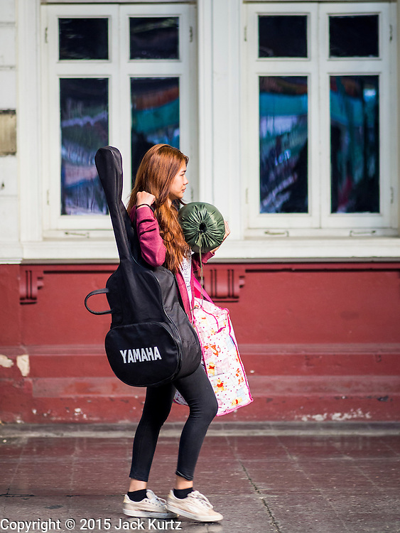 04 JANUARY 2015 - BANGKOK, THAILAND:  A woman arriving in Bangkok carries her luggage and guitar through the Bangkok train station. Millions of Thais hit the road Sunday returning to Bangkok after the long weekend New Year holiday. Train stations and trains were packed and the state owned bus company scheduled thousands of extra buses to handle the demand.   PHOTO BY JACK KURTZ