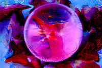 magnification of particular in a multicolored dappled background. In the center a crystal sphere magnificates a particular highlighting violet colors and shades.