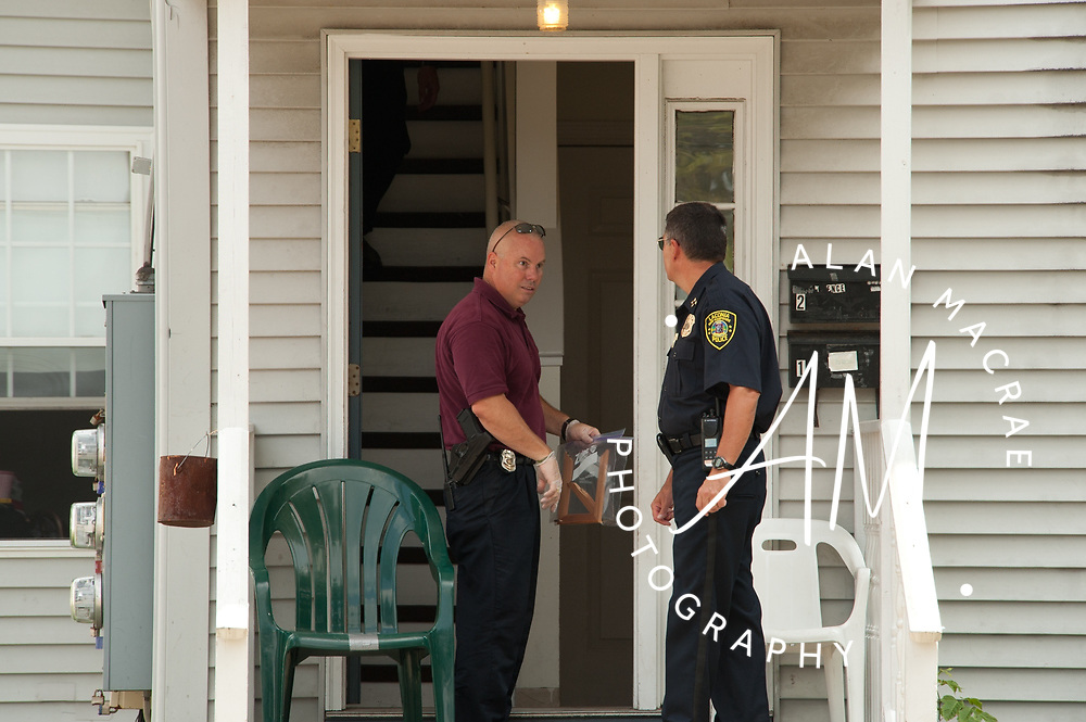 Laconia Police Chief Michael Moyer, left, confers with Detective Kevin Butler at the scene of Wednesday morning's shooting at 345 South Main Street.  {Alan MacRae/for the Citizen)