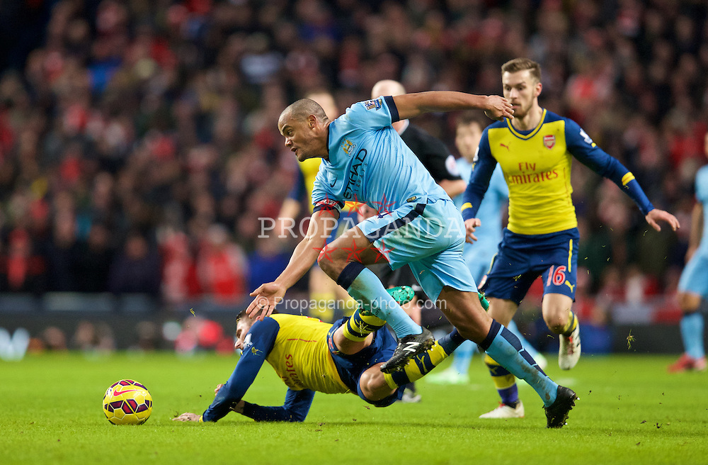 MANCHESTER, ENGLAND - Sunday, January 18, 2015: Manchester City's captain Vincent Kompany is shown a yellow card for this tackle against Arsenal during the Premier League match at the City of Manchester Stadium. (Pic by David Rawcliffe/Propaganda)