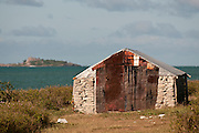 Small stone building with tin sheet roof.